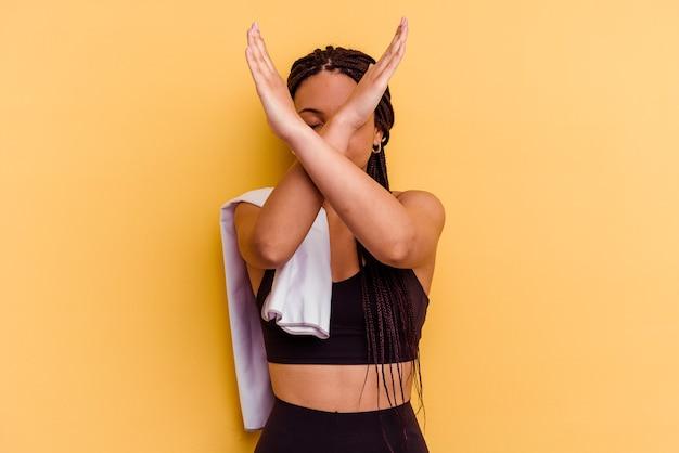 Jonge sport afrikaanse amerikaanse vrouw die een handdoek houdt die op gele muur wordt geïsoleerd die twee wapens gekruist, ontkenningsconcept houdt.