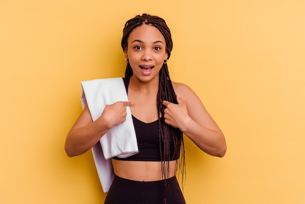 Jonge sport afrikaanse amerikaanse vrouw die een handdoek houdt die op gele muur wordt geïsoleerd verrast wijzend met vinger, breed glimlachend.
