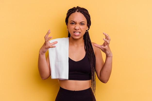 Jonge sport afrikaanse amerikaanse vrouw die een handdoek houdt die van streek schreeuwen met gespannen handen.