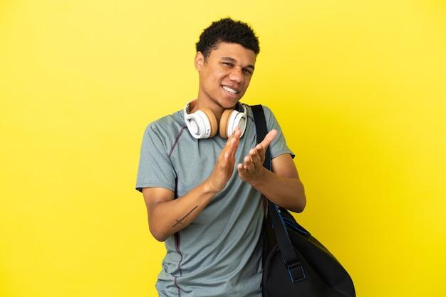 Jonge sport afro-amerikaanse man met sporttas geïsoleerd op gele achtergrond applaudisseren na presentatie in een conferentie