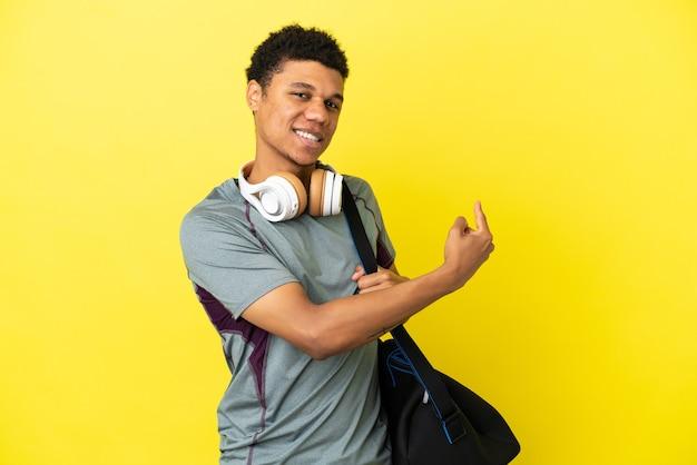 Jonge sport afro-amerikaanse man met sporttas geïsoleerd op gele achtergrond die terug wijst