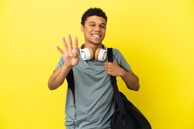 Jonge sport afro-amerikaanse man met sporttas geïsoleerd op gele achtergrond gelukkig en vier tellen met vingers