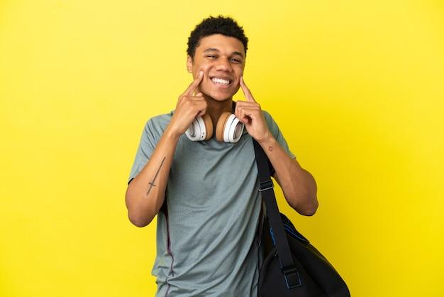 Jonge sport afro-amerikaanse man met sporttas geïsoleerd op gele achtergrond glimlachend met een vrolijke en aangename uitdrukking