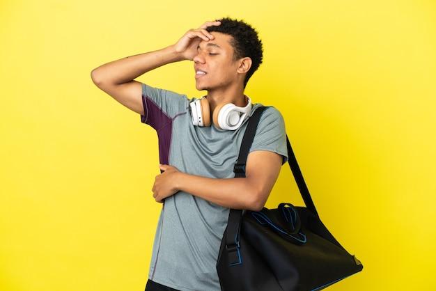Jonge sport afro-amerikaanse man met sporttas geïsoleerd op gele achtergrond heeft iets gerealiseerd en is van plan de oplossing