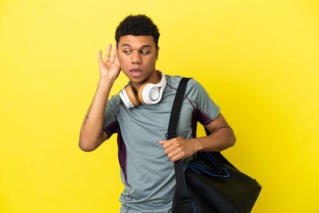 Jonge sport afro-amerikaanse man met sporttas geïsoleerd op gele achtergrond luisteren naar iets door hand op het oor te leggen