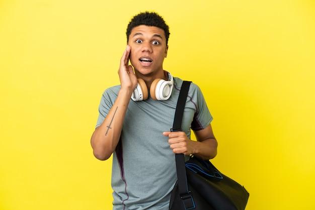 Jonge sport afro-amerikaanse man met sporttas geïsoleerd op gele achtergrond met verrassing en geschokte gezichtsuitdrukking