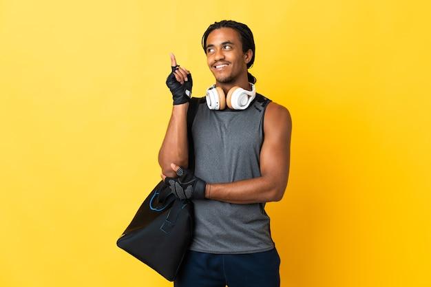 Jonge sport afro-amerikaanse man met vlechten met zak geïsoleerd op gele achtergrond een geweldig idee omhoog