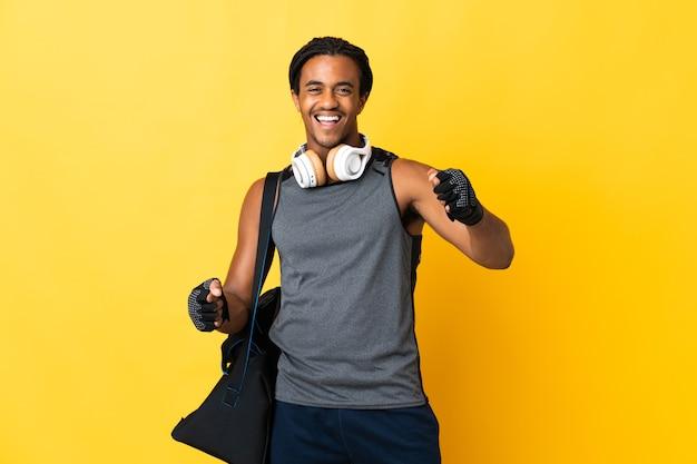 Jonge sport afro-amerikaanse man met vlechten met zak geïsoleerd op gele achtergrond een overwinning vieren