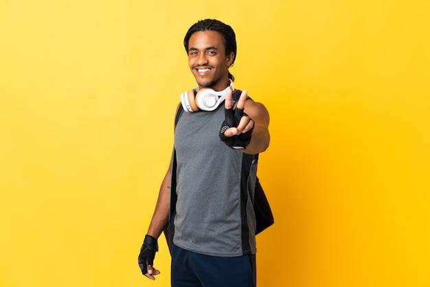 Jonge sport afro-amerikaanse man met vlechten met zak geïsoleerd op gele achtergrond glimlachend en overwinning teken tonen