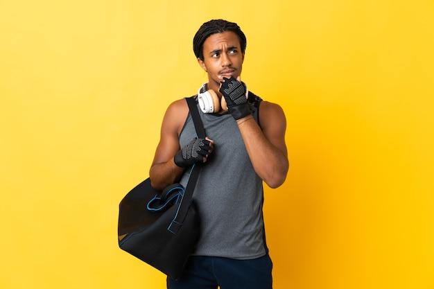 Jonge sport afro-amerikaanse man met vlechten met zak geïsoleerd op gele achtergrond twijfels