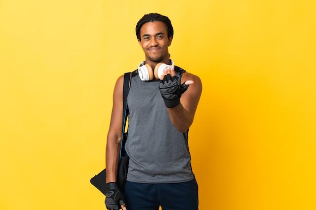 Jonge sport afro-amerikaanse man met vlechten met zak geïsoleerd op gele achtergrond uitnodigend om met de hand te komen. blij dat je gekomen bent
