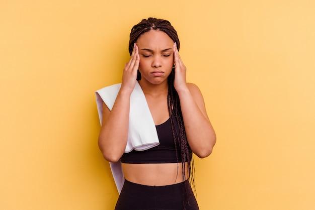 Jonge sport afro-amerikaanse vrouw met een handdoek geïsoleerd op geel tempels aan te raken en hoofdpijn te hebben.