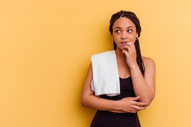 Jonge sport afro-amerikaanse vrouw met een handdoek geïsoleerd op gele achtergrond ontspannen denken aan iets kijken naar een kopie ruimte.
