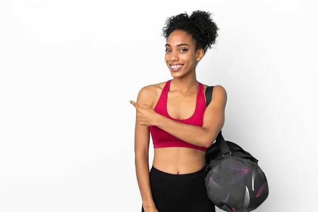 Jonge sport afro-amerikaanse vrouw met sporttas geïsoleerd op een blauwe achtergrond die terug wijst