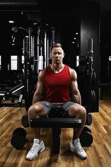 Jonge sport atleet fitness model in de sportschool schudt zijn biceps met halters. sportmotivatie, low key, hoog contrast. het concept van een gezonde levensstijl, levensbeweging, kopie ruimte.