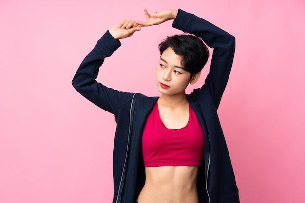 Jonge sport aziatische vrouw die zich uitstrekt