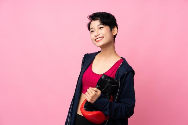 Jonge sport aziatische vrouw over geïsoleerde roze muur met bokshandschoenen