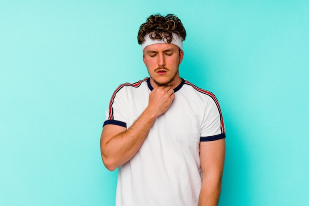 Jonge sport blanke man geïsoleerd op blauwe achtergrond lijdt pijn in de keel als gevolg van een virus of infectie.