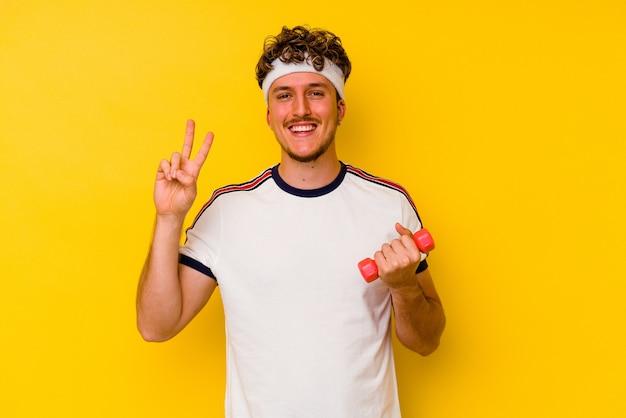 Jonge sport blanke man met een halter geïsoleerd op een gele muur met nummer twee met vingers.