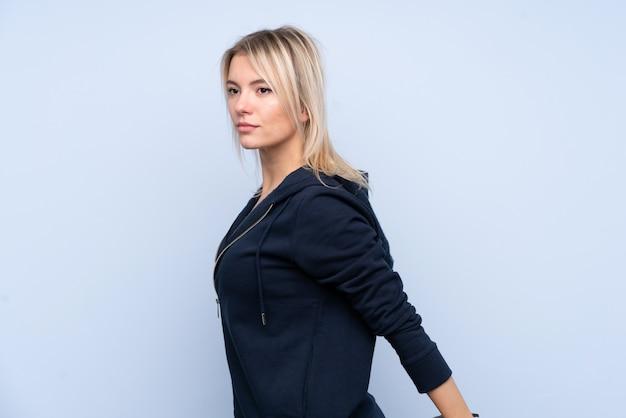 Jonge sport blonde vrouw over geïsoleerd blauw muur het uitrekken zich been