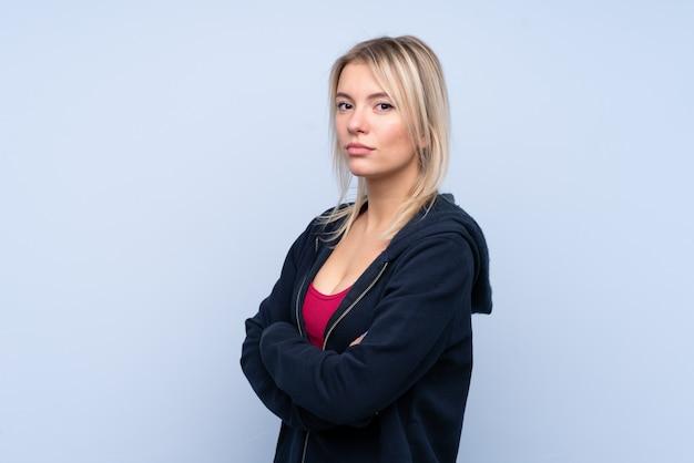 Jonge sport blonde vrouw over geïsoleerde blauwe muur die de wapens gekruist houdt