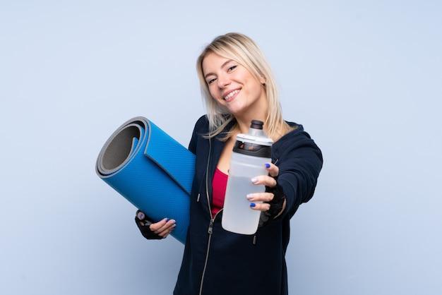 Jonge sport blonde vrouw over geïsoleerde blauwe muur met de fles van het sportenwater en met een mat