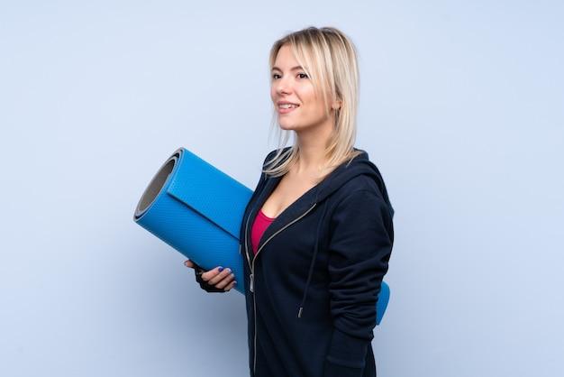 Jonge sport blonde vrouw over geïsoleerde blauwe muur met een mat