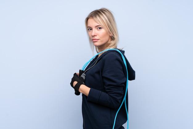 Jonge sport blonde vrouw over geïsoleerde blauwe muur met touwtjespringen