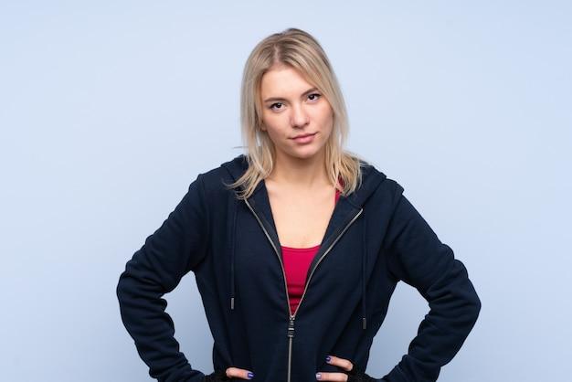Jonge sport blonde vrouw over geïsoleerde blauwe muur poseren met armen op heup