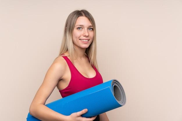 Jonge sport blonde vrouw over geïsoleerde muur met een mat en het glimlachen