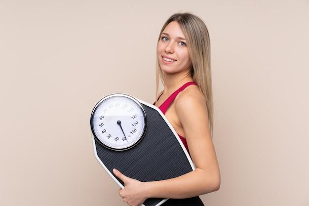 Jonge sport blonde vrouw over geïsoleerde muur met weegmachine