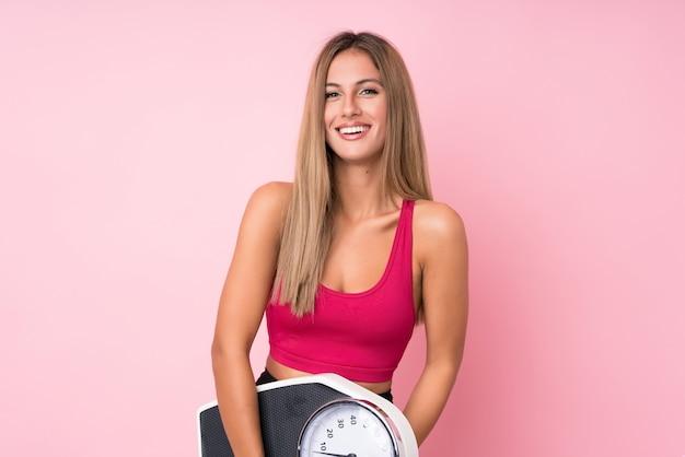 Jonge sport blonde vrouw over geïsoleerde roze muur met weegmachine