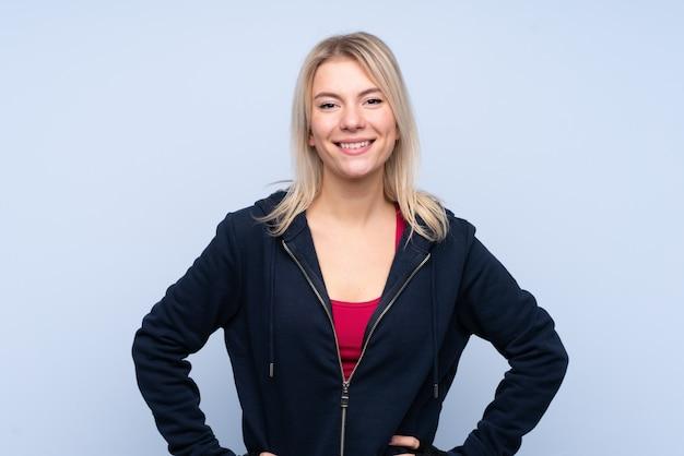 Jonge sport blonde vrouw over het geïsoleerde blauwe muur stellen met wapens bij heup en het glimlachen