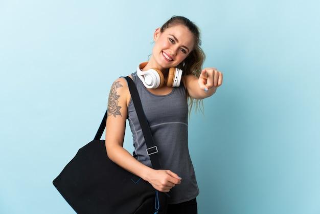 Jonge sport braziliaanse vrouw met sporttas geïsoleerd op blauw wijzend front met gelukkige uitdrukking