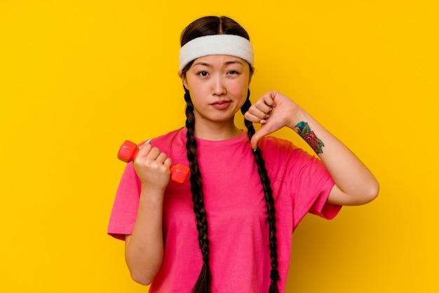 Jonge sport chinese vrouw die een afkeergebaar, duimen naar beneden toont. meningsverschil concept.