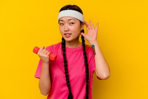 Jonge sport chinese vrouw die een roddel probeert te luisteren.