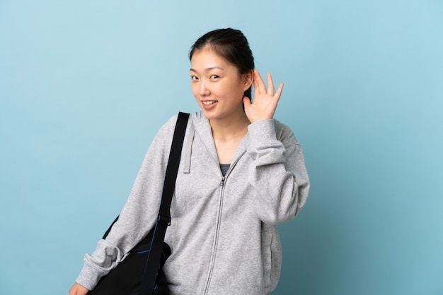 Jonge sport chinese vrouw die met sporttas over geïsoleerd blauw aan iets luistert door hand op het oor te leggen