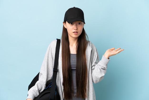 Jonge sport chinese vrouw die met sporttas over geïsoleerd blauw twijfelsgebaar maakt