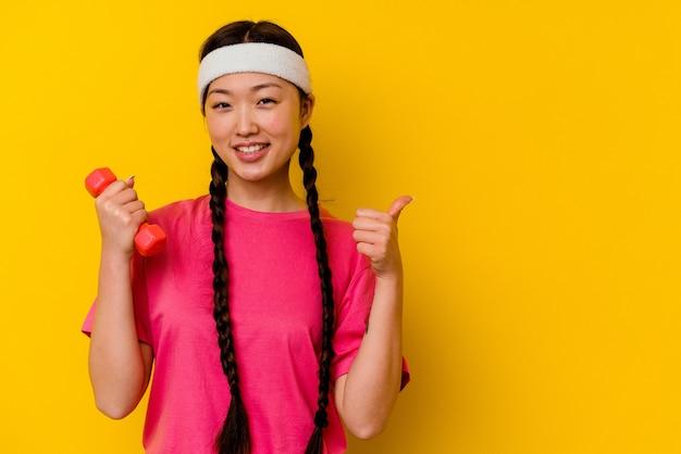 Jonge sport chinese vrouw die op gele muur wordt geïsoleerd die en duim glimlacht opheft