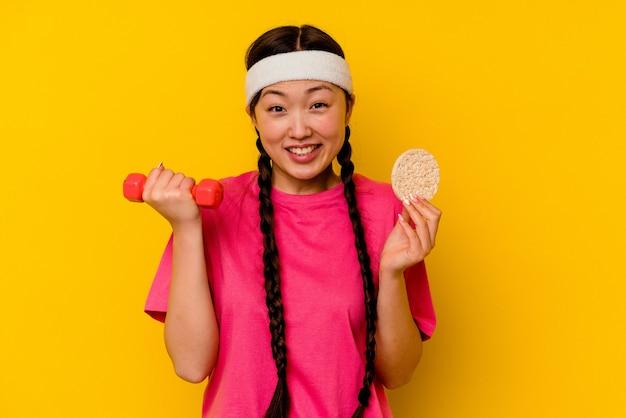 Jonge sport chinese vrouw die rijstwafels eet die op gele achtergrond worden geïsoleerd
