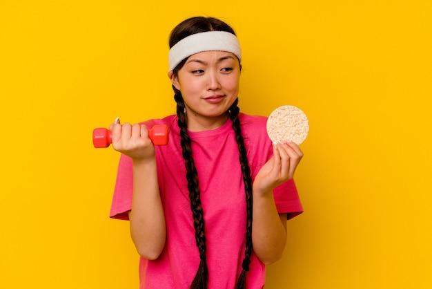 Jonge sport chinese vrouw die rijstwafels eet die op gele muur worden geïsoleerd