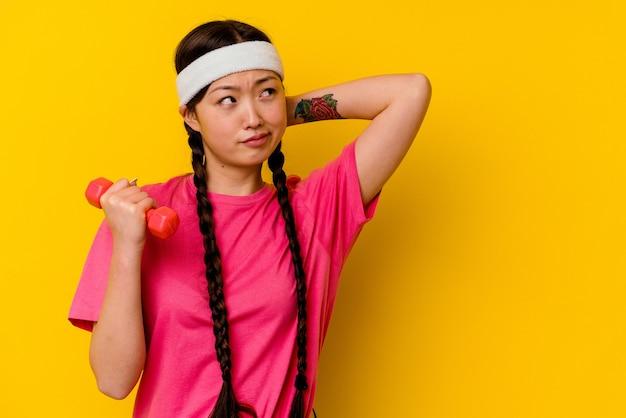 Jonge sport chinese vrouw geïsoleerd op gele muur achterkant van het hoofd aanraken, denken en een keuze maken.