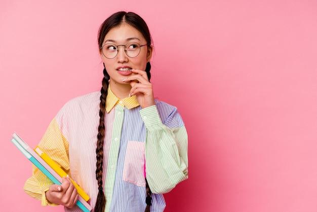 Jonge sport chinese vrouw geïsoleerd op gele muur ontspannen denken aan iets kijken naar een kopie ruimte.