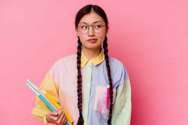 Jonge sport chinese vrouw geïsoleerd op gele muur verward, twijfelachtig en onzeker.