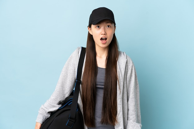 Jonge sport chinese vrouw met sporttas over blauwe muur die omhooggaand en met verraste uitdrukking kijkt
