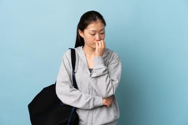 Jonge sport chinese vrouw met sporttas over blauwe muur die twijfels heeft