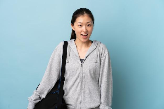 Jonge sport chinese vrouw met sporttas over blauwe muur met verrassingsgelaatsuitdrukking