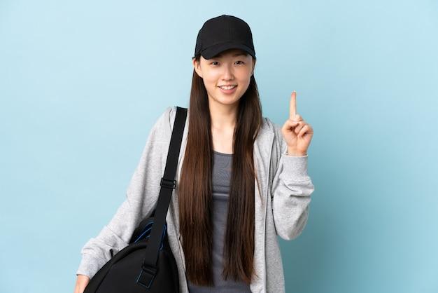 Jonge sport chinese vrouw met sporttas over geïsoleerd blauw dat een geweldig idee benadrukt