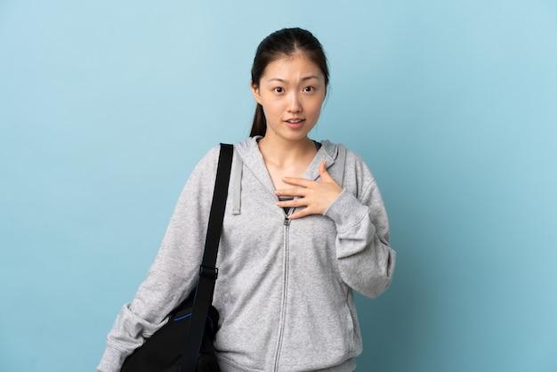 Jonge sport chinese vrouw met sporttas over geïsoleerd blauw dat naar zich richt