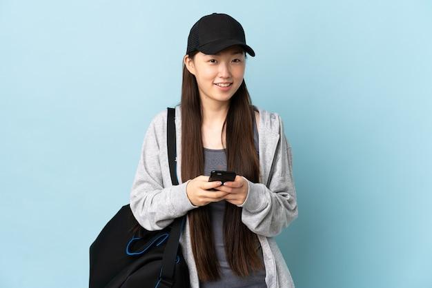 Jonge sport chinese vrouw met sporttas over geïsoleerd blauw die een bericht met mobiel verzendt
